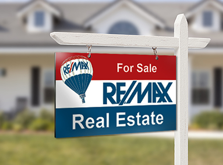 Red For Sale Real Estate Sign in Front of Beautiful New Home.